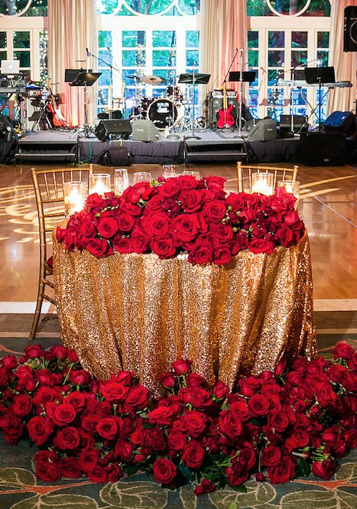 a sweetheart table with a gold sequin tablecloth and lots of red roses and greenery on the table and on the floor