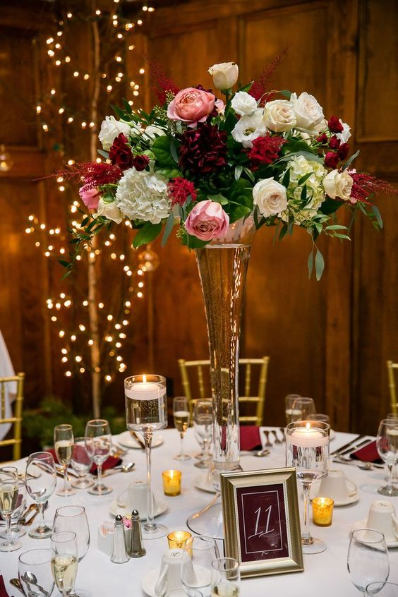 a tall glass vase with white, burgundy and pink blooms and greenery is a stylish and chic floral centerpiece to try