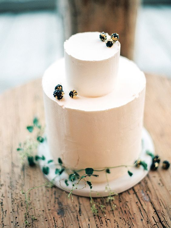 a textural buttercream wedding cake topped with foliage and with gilded berries