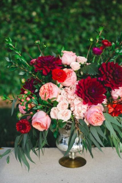 a vibrant floral centerpiece of a vintage vase with blush, red and burgundy blooms and greenery for a Valentine wedding
