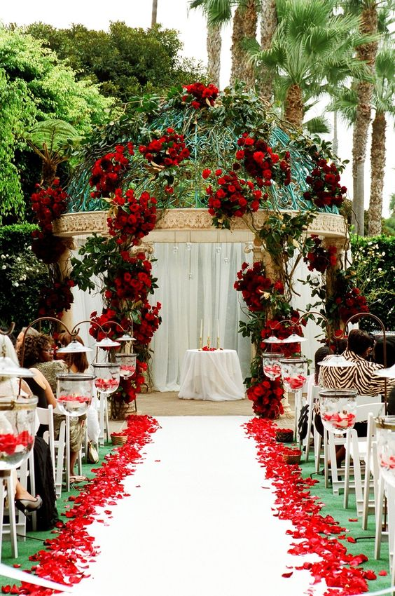 a wedding altar done with red roses, greenery and red rose petals on the floor is a fantastic idea for Valentine's Day