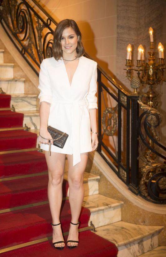 a white blazer mini dress with short sleeves and a deep neckline, black shoes, a black necklace and a shiny mini clutch