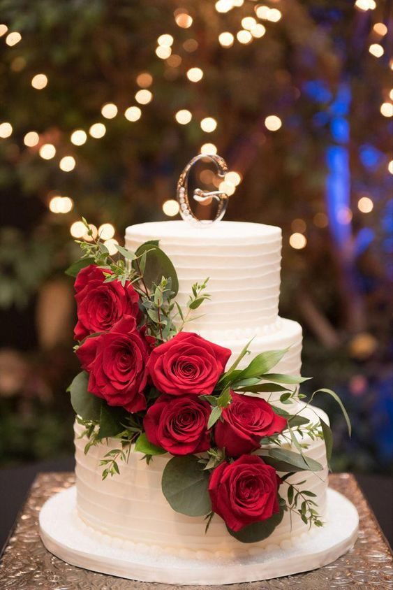 a white buttercream wedding cake topped with red roses, greenery and a silver monogram is a lovely dessert