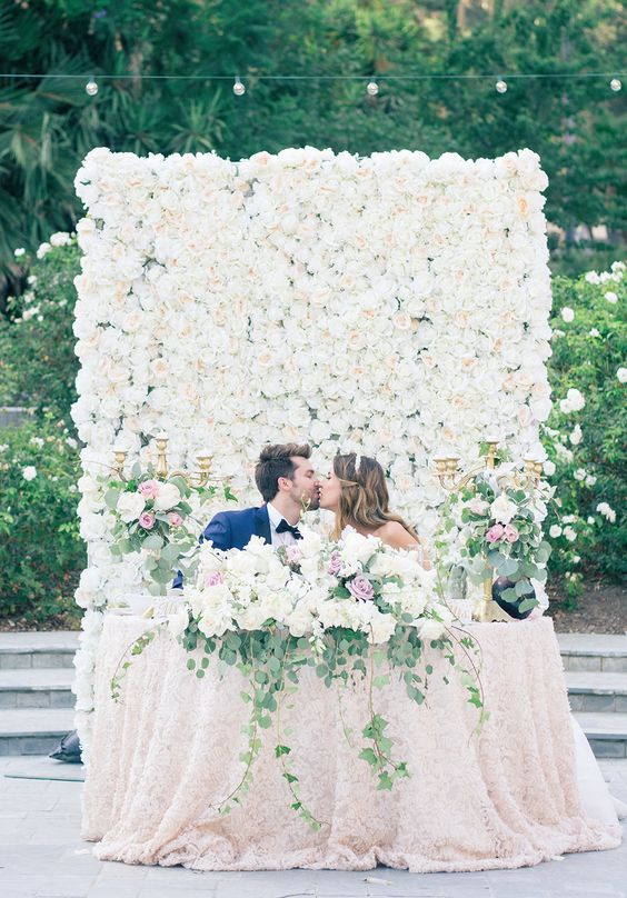 a white flower wall that is used as a backdrop for the ceremony and for the reception