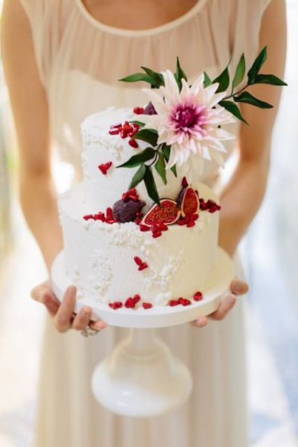 a white pattermed wedding cake with figs, red pomegranate sees, a blush flower and greenery for a Valentine wedding