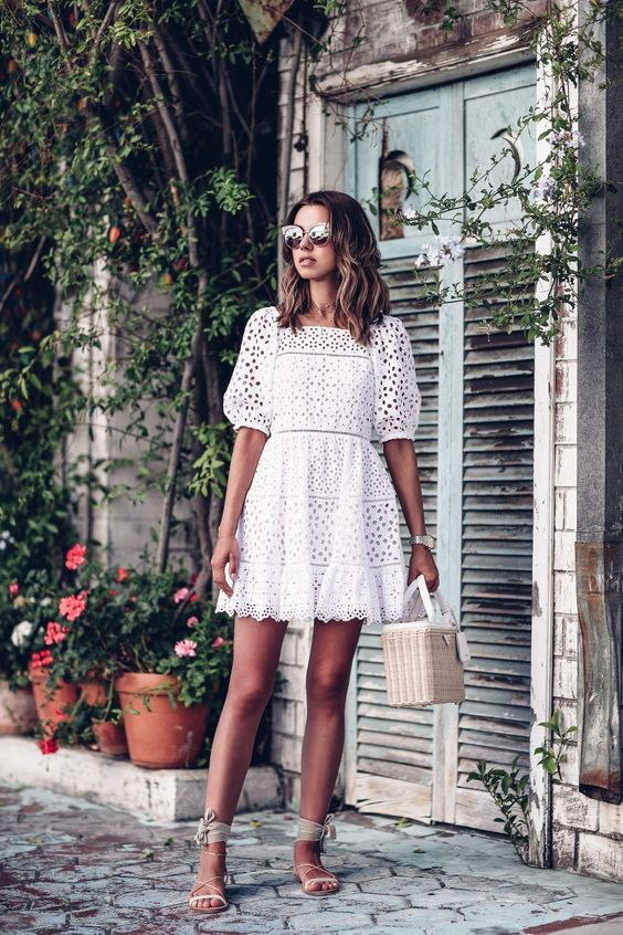 a white perforated mini dress with a straight neckline, short sleeves, neutral sandals and a basket bag for a tropical wedding