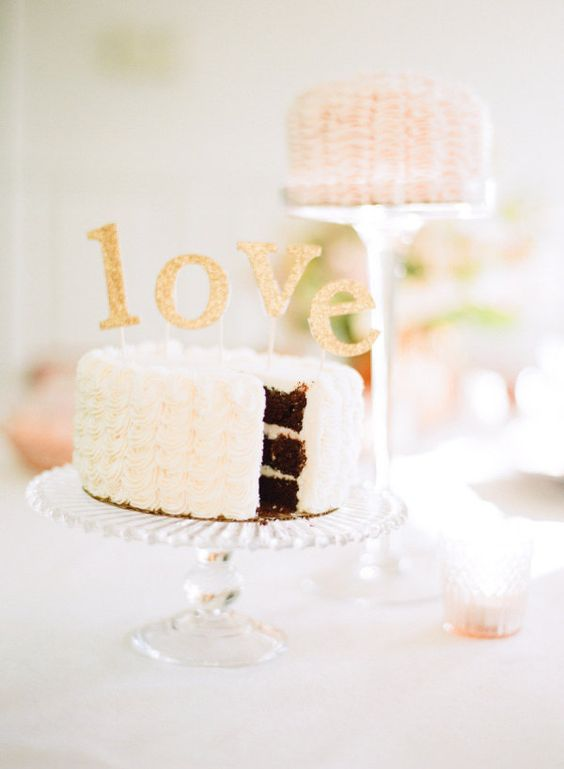 a white ruffled wedding cake with gold glitter letters on top is a beautiful and cute idea for a Valentine's Day