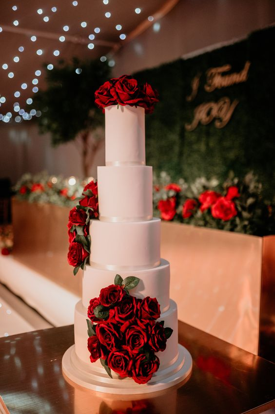 a white wedding cake decorated with red roses is timeless classics that brings much romance and elegance