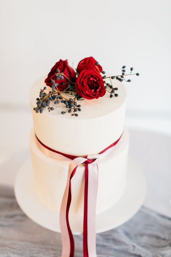 a white wedding cake topped with privet berries, red blooms and a striped blush and red ribbon for a Valentine wedding