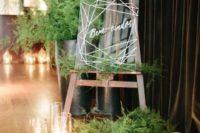 acrylic wedding signage with much fern around and pillar candles for a modern wedding