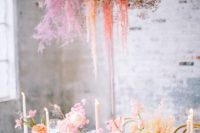 an ethereal and romantic Valentine's Day wedding table with blush blooms, grasses, candles, blooms as favors and a dried bloom and berry installation
