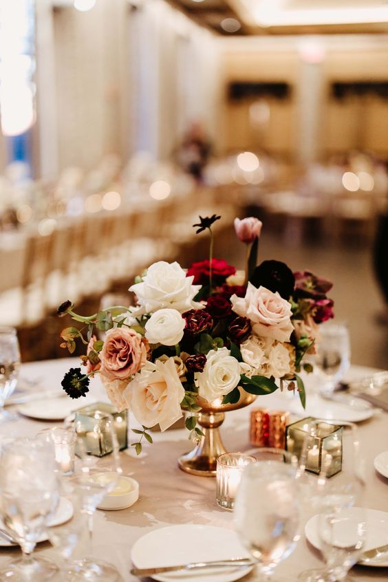 an exquisite Valentine wedding centerpiece of white, blush and deep purple blooms and leaves is adorable