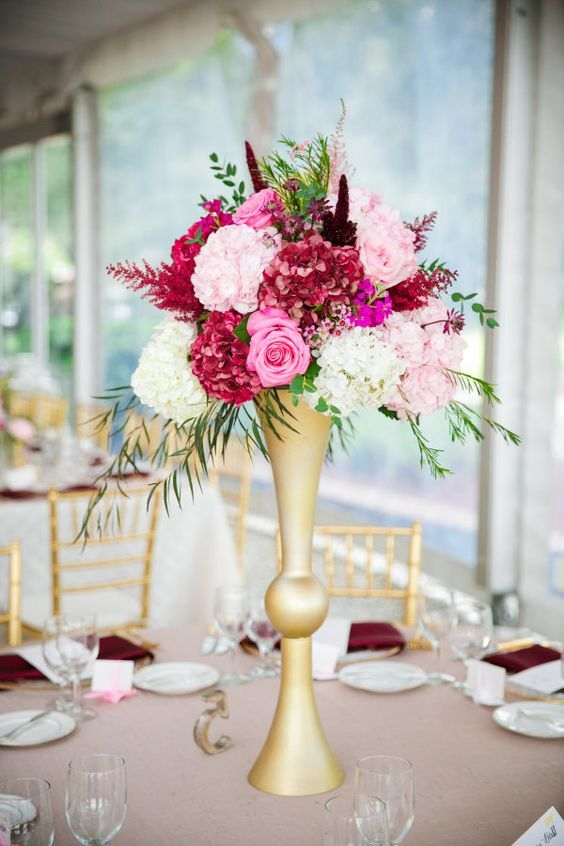 an exquisite Valentine's Day wedding centerpiece of a gold stand with pink, fuchsia and burgundy blooms and greenery is wow
