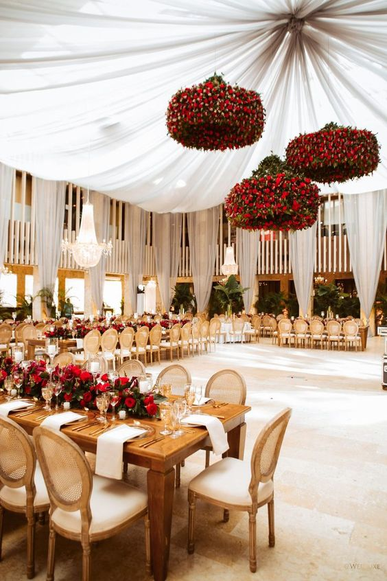 an exquisite Valentine's Day wedding venue with jaw-dropping red rose chandeliers and a red rose table runner with greenery