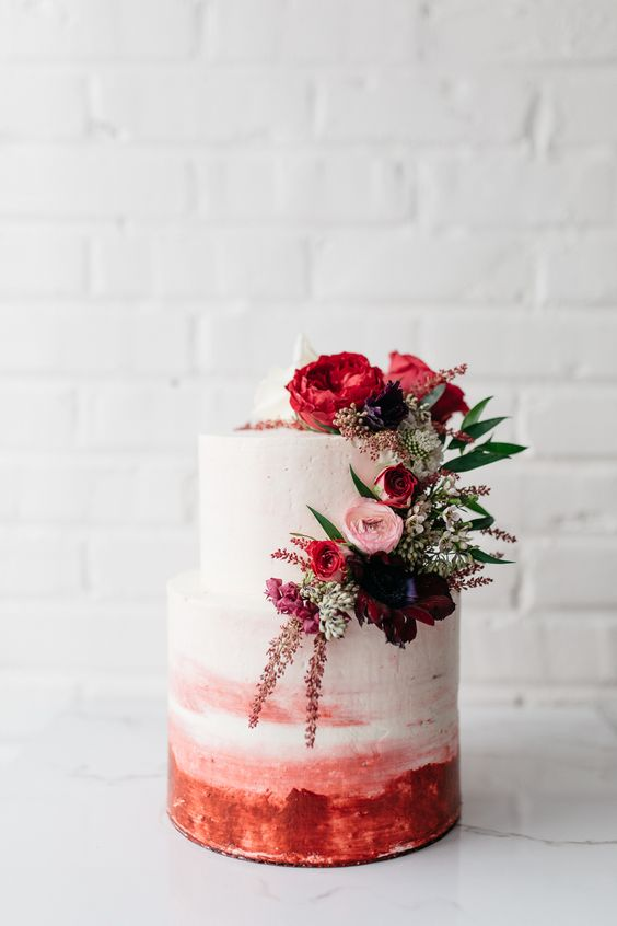 an ombre watercolor pink and red wedding cake topped with beautiful red, pink and purple blooms and greenery
