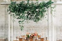 an overhead greenery installation over the reception is a trendy decor idea and brings a fresh feel indoors