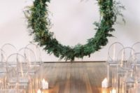 an oversized circular greenery wedding arch floating in the air, ghost chairs and candles