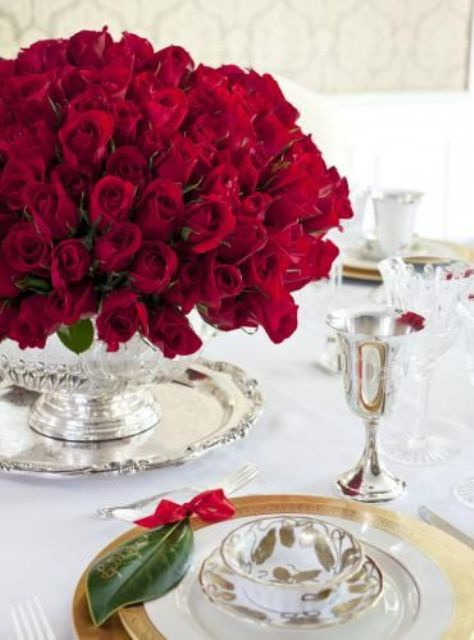 an oversized red rose centerpiece in a silver vase is a gorgeous and refined idea for a Valentine's Day wedding