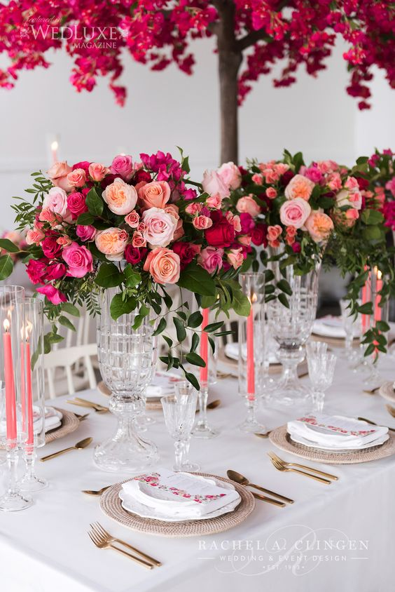 bold Valentine wedding centerpiece of light pink, fuchsia, peachy and red blooms and greenery is fantastic