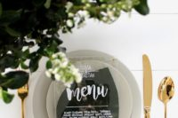 greenery, matte grey dishes and an acrylic menu for a chic minimalist look with a shiny touch