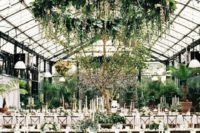 lush and large greenery chandelier with cascading elements and a living wall turn an indoor space into an outdoor one