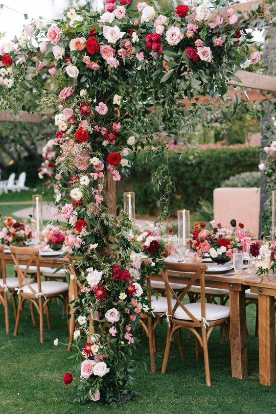 red, pink and blush roses plus greenery for decorating the wedding table and an arch over it is a lovely idea