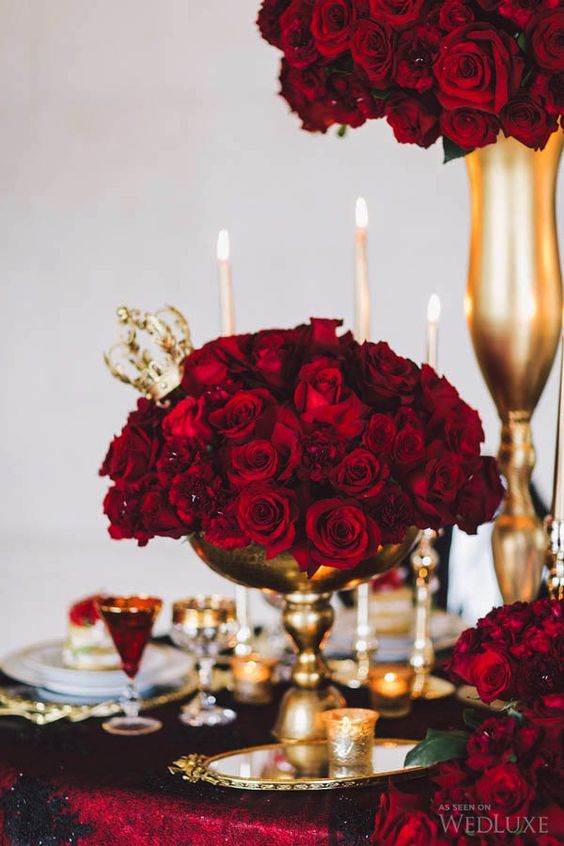 red rose arrangements in gold vases, with gold candleholders and glasses for a Valentine's Day tablescape