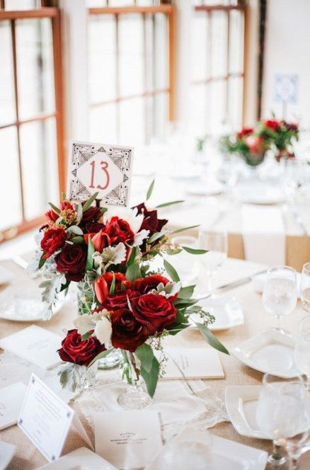 simple red rose centerpieces with usual and pale greenery and an art deco table number for a Valentine's Day