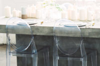 transparent chairs and a concrete table with lots of white pillar candles for a minimalist tablescape