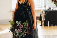 a Halloween bride wearing an A-line black wedding dress with a lace bodice with straps, a sheer skirt and tall lace boots