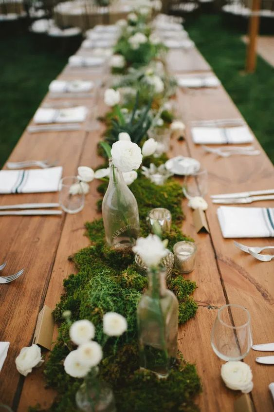 a beautiful backyard wedding tablescape with a moss and white bloom runner, striped napkins and chic candleholders is a lovely idea
