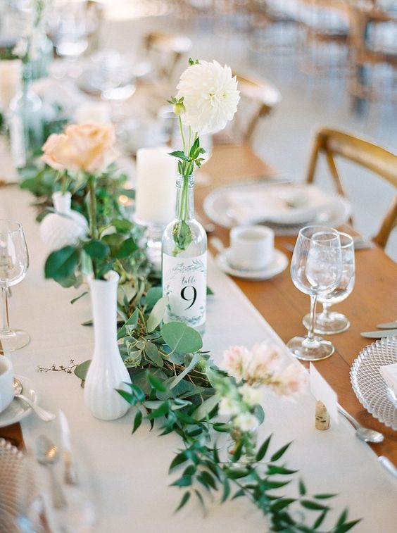 a beautiful backyard wedding tablescape with a neutral runner, greenery, pastel and white blooms and crystal chargers