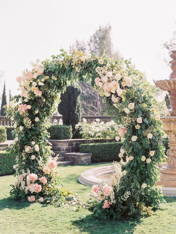 a beautiful circle wedding arch completely covered with greenery and with blush blooms