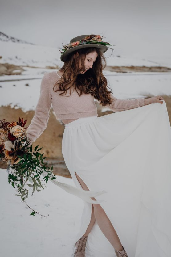 a blush crop top sweater with long sleeves, a white pleated skirt, tan booties and a grey hat decorated with fresh blooms