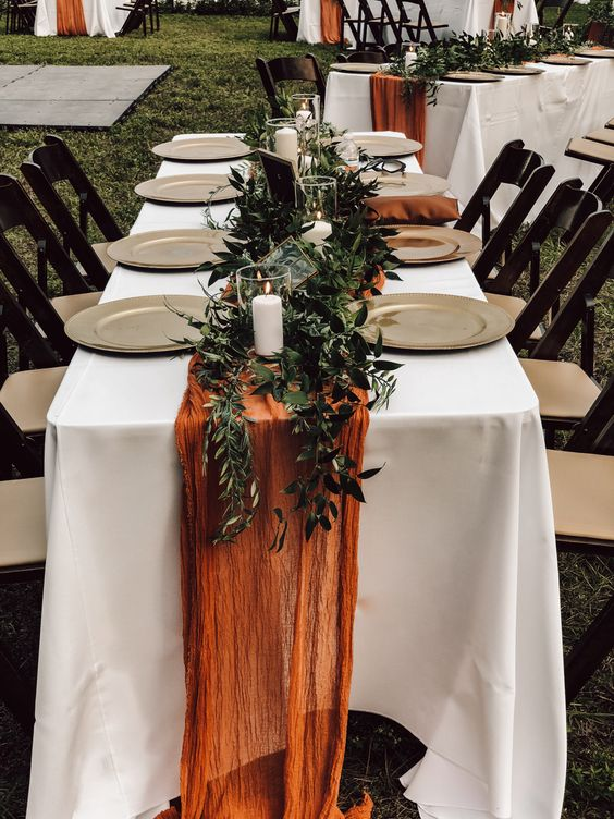 a boho fall backyard wedding tablescape with metal chargers, a lush greenery runner and candles, a rust-colored runner is a bold and cool solution