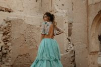 a bold bridal look with a crop embellished top with short sleeves and a mint-colored wedding skirt with a train