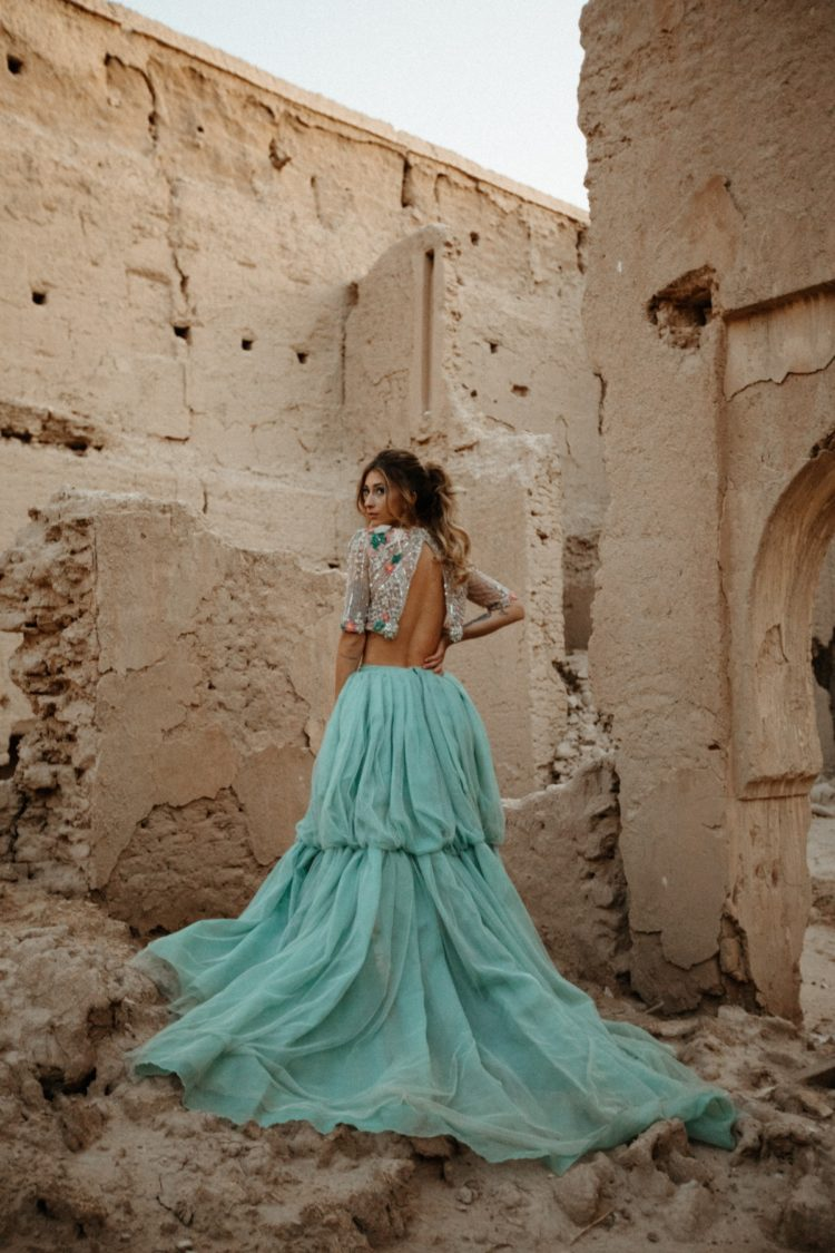 a bold bridal look with a crop embellished top with short sleeves and a mint colored wedding skirt with a train