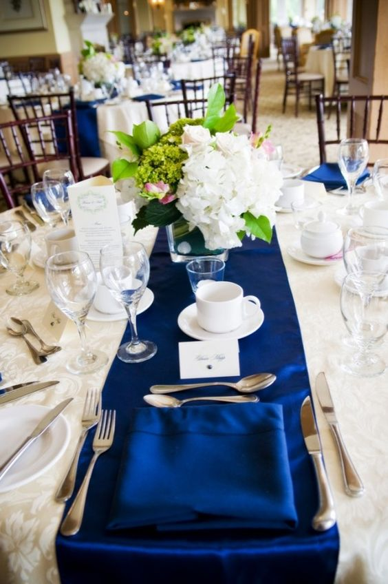 a bold table setting with a navy table runner, a white floral centerpiece with greenery and white candles