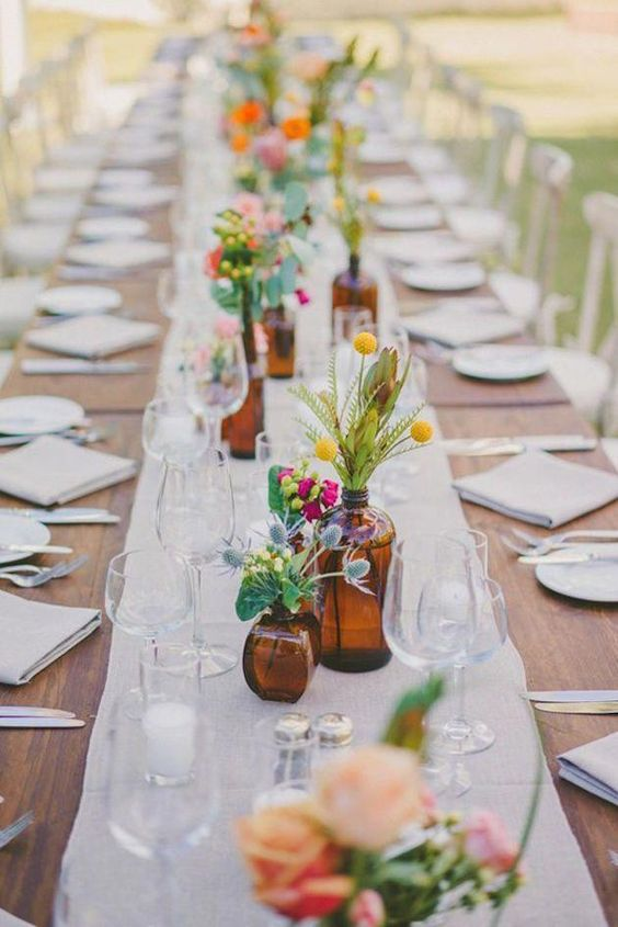 a bright and cute backyard wedding tablescape with neutral linens, bold floral arrangements and candles is a cool idea