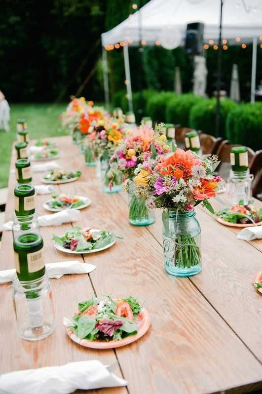 a bright and simple backyard wedding tablescape with bold floral arrangements in bluejars, with bright plates and neutral linens