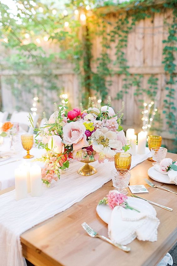 a bright backyard wedding table setting with pink and fuchsia blooms, amber glasses and candles plus neutral linens