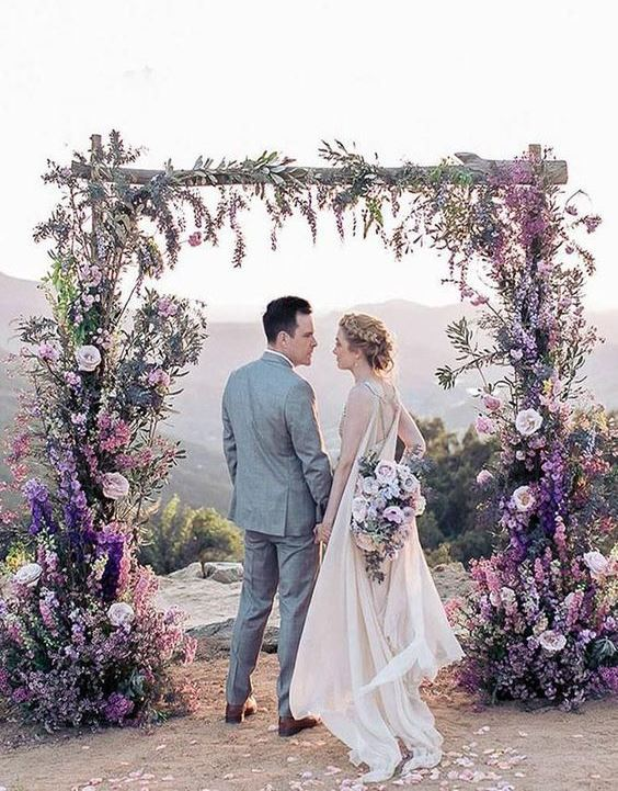 a bright lilac and purple wedding arch comepletely covered with blooms all over