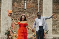 a bright orange off the shoulder ruffle wedding dress with a train and a colorful floral crown