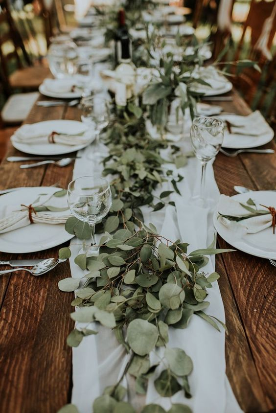 a carefree backyard wedding table setting with neutral linens and a lush eucalytus runner plus candles is a lovely idea