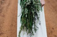 a cascading super long wedding bouquet of various types of foliage and some thistles and blooming branches looks wow