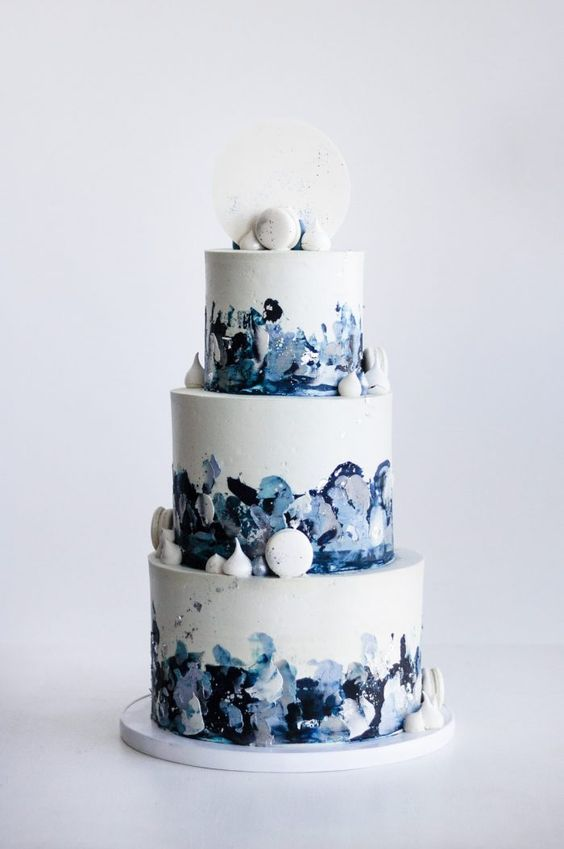 a catchy navy, blue and white wedding cake with brushstrokes and white macarons and meringues for decor