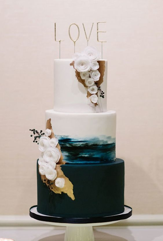 a catchy wedding cake with a white tier, a brushstroke one and a plain one, with white sugar blooms, gold touches and berries