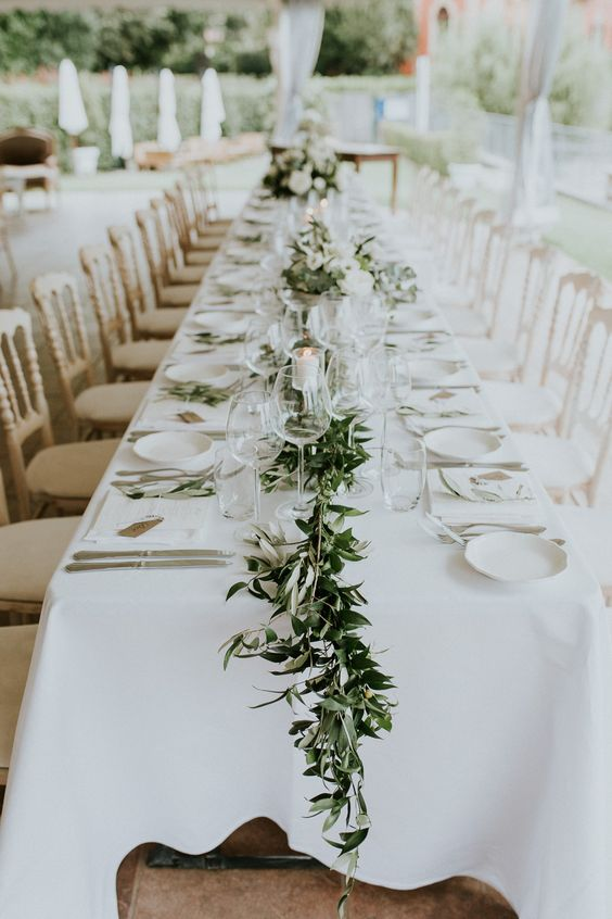 a chic backyard wedding table setting with white linens and plates, with a greenery runner dotted with candles and silver cutlery