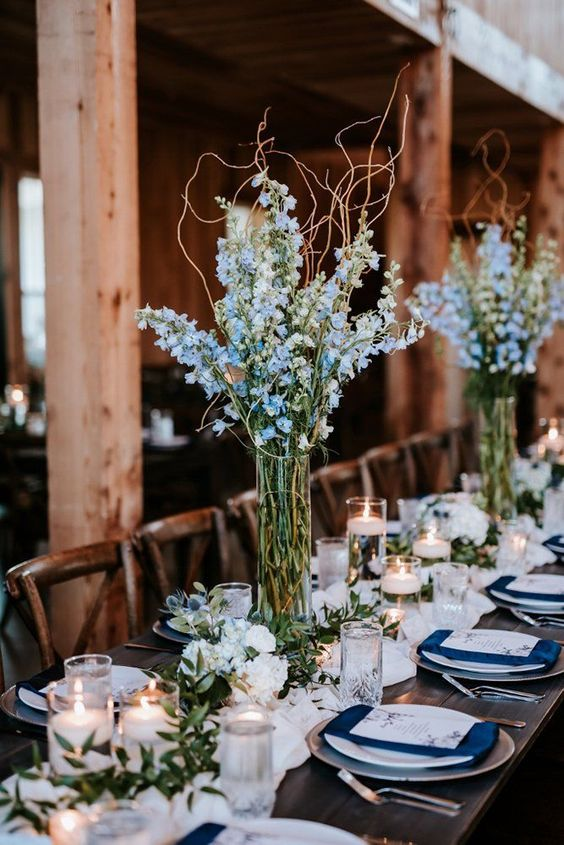a chic navy and white tablescape with navy napkins, a white table runner, blue floral centerpiece, white floral garlands and candles