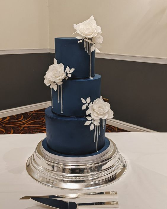 a chic navy wedding cake with large white roses and leaves looks breathtakingly elegant